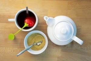 Infused tea, teapot and brown sugar next to each other on beech wood, shot from top